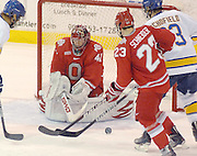 OSU goaltender Dustin Carlson fends off the puck during a scrum in front of the net during the second period of the Buckeyes 3 -2 loss to the LSSU Lakers at Taffy Abel Arena in Sault Ste. Marie.
