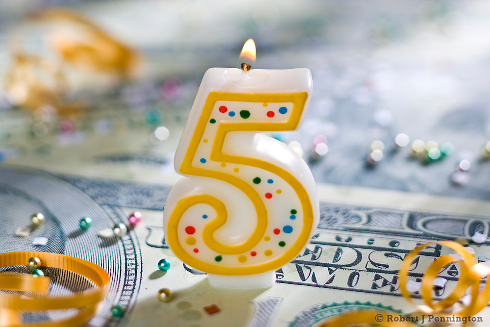 Five (5) year celebration candle on U.S. currency.