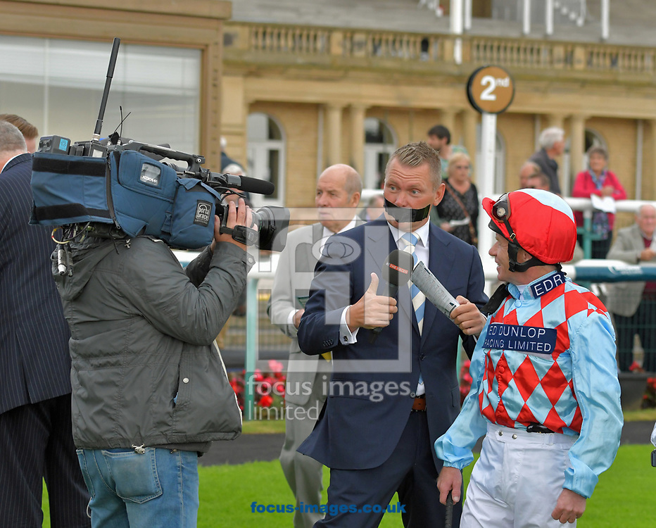Horse racing presenter Matt Chapman with his mouth covered by gaffer tape to raise money for Voice Of Racing Charity day interviews jockey Jimmy Quinn before race 1 at the 188 Bet Summer Afternoon meeting at Doncaster Racecourse, Doncaster<br /> Picture by Martin Lynch/Focus Images Ltd 07501333150<br /> 30/06/2017
