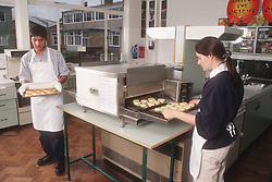 Secondary school pupils baking scones during home economics lesson,