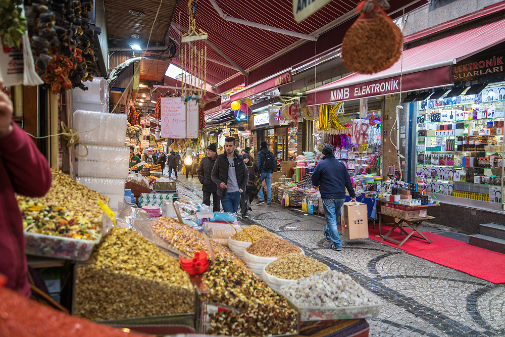 View out from storefront for a spice shop as people walk up and down pathway at outdoor marketplace, Istanbul, Turkey.