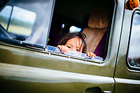 A young child peeks out of a car window on the road in northern Mongolia.