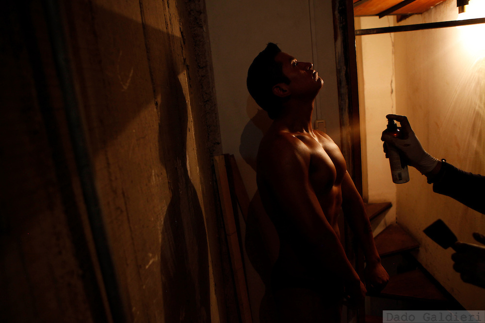 A bodybuilder is sprayed with professional tan lotion before competing in a regional bodybuilding championship in La Paz, Saturday, April 10, 2010.