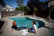University of California, Merced students Jill Foster, left, and Heather Alarab, right, sit by the pool at the spacious rental home they share in Merced, Calif., October 29, 2011.