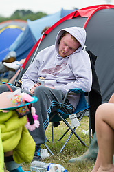 © Licensed to London News Pictures. 12/06/2015. Isle of Wight, UK.  A festival goer sleeps outside his tent at amongst his friends at the Isle of Wight Festival 2015 on  the morning of  Friday Day 2, after a late night of enjoyment.     Yesterday the weather was hot and Sunny.  Today rain is forecast.  This years festival include headline artists the Prodigy, Blur and Fleetwood Mac.  Photo credit : Richard Isaac/LNP