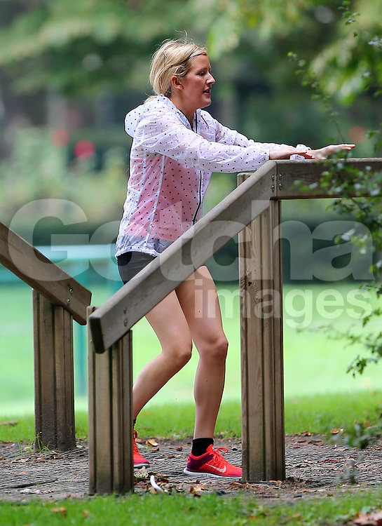 Singer Ellie Goulding keeping fit whilst working out in a London park with a personal trainer.  The 'Burn' singer wearing black shorts a waterproof jacket over a pink strap top and trainers, was seen sprinting on the track and field and also using the climbing apparatus. London. UK. 04/09/2014<br />