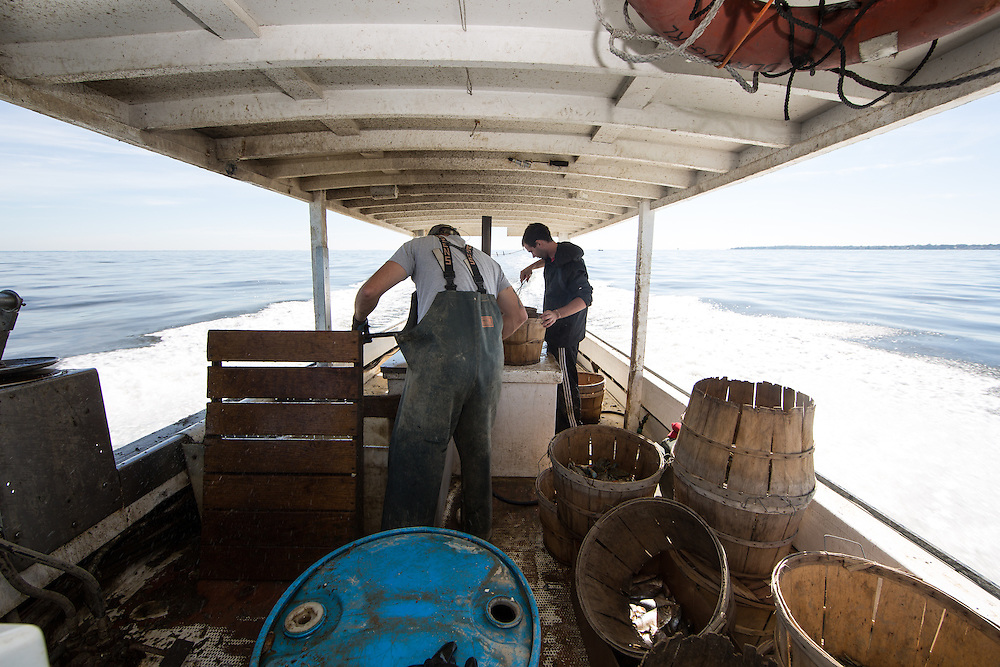 Ryan Ribb and Chris Shipley clean up the boat and secure the tops on the baskets filled with crab as they head home.   October 11, 2015