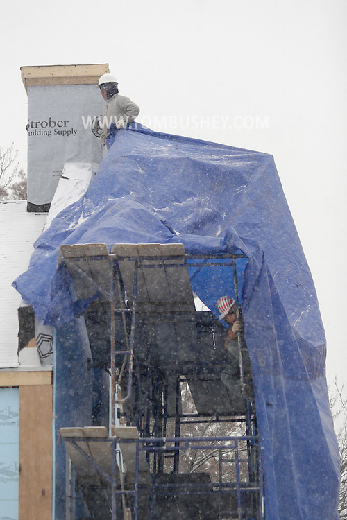 Newburgh , NY - Workers spread a tarp over a scaffolding on the side of a dormitory under construction at Mount Saint Mary College in Newgburgh during a snowstorm on  Dec. 7, 2007.