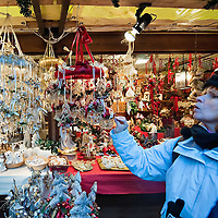 VERONA, ITALY - DECEMBER 04:  A shoper checks Christmas decorations in a wodden hut at the Verona Christmas Market on December 4, 2010 in Verona, Italy. Christmas markets, fairs, lights and nativity scenes fill Northern Italian cities and villages from December through January 6.