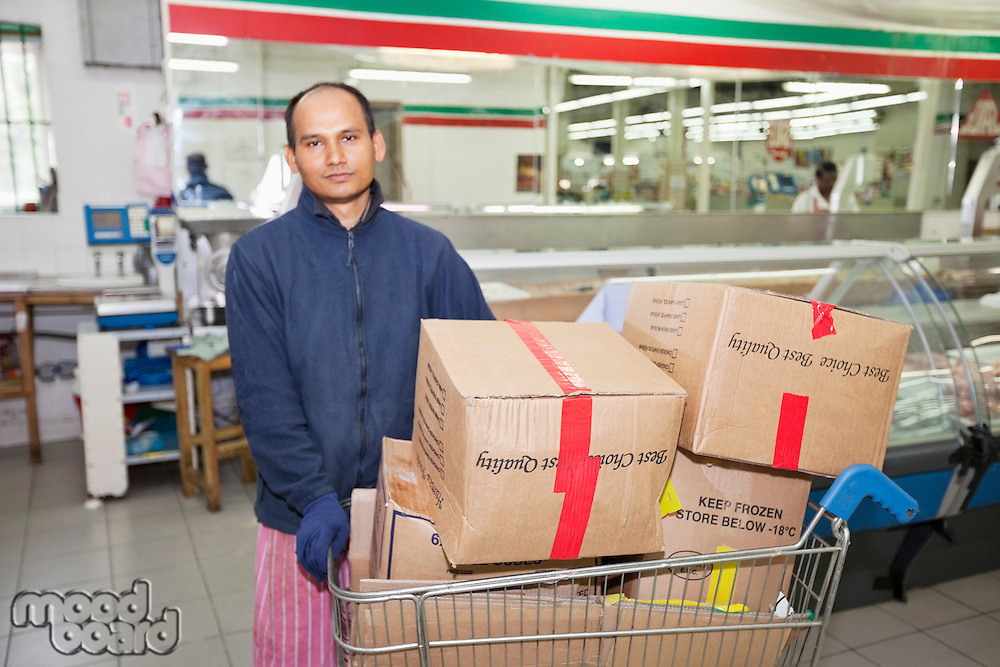 Portrait of male worker with shopping cart