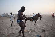 "Papa Sow (left) and Ouza (right), two professional Lamb's wrestler, from Ecurie Fass team, are perfoming hard training, fighting against each other on the beach. Parcelles, north Dakar, Senegal, on tuesday, April 07 2009.....""Lamb, the wolof word for fight, is a very popular type of African wrestling in Senegal. This ""lutte traditionelle"" has been transformed into a national cult, drawing massive following next only to football. Senegalese wrestlers are among the best-known national sports figures. The senegalese fight form allows blows with the hands (frappe), the only of the West African to do so. The lutteurs wrestle in a sandy arena and attempt to win by making their opponent's knees, shoulder, or back touch the sand. Matches are festive and lively occasions, with music, dancing, and praise singing for the athletes; the actual wrestling bouts, however, are often over within a few seconds. Presently, wrestling is arranged by business-promoters who offer prizes for the winners..The sport has produced its own legends, names such as Yékini, Tyson and Bombardier (stage names) are celebrities in Senegal. In particular Mohammed Ndao, aka Tyson,  the 34-year-old leader of the Boul Falé generation of Pikine, a Dakar suburb, did not only revolutionise the sport, by carving his own group identity, and upsetting the old guard, but he is also credited with insisting on commensurate remuneration for the wrestlers. A ""combat"" could start from 10 million CFA francs (about 20,000 US dollars) to 65 million CFA francs. (about 130,000 dollars). The phenomenal success is such that stakeholders are already talking about building a separate stadium for the sport in the country."""