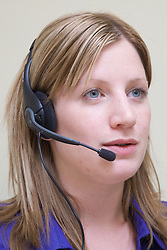 Office worker using a hands free telephone headset whist talking to a customer on the phone,
