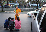 Three young girls receive a blessing from a Buddhist monk on the side of the road in Chiang Mai Thailand.