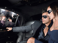 Couple in evening wear and sunglasses in back of limousine paparazzi at car window