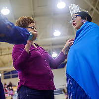Laurenda Silversmith pins a prize shawl to Ymelda Coriz as Coris is named Miss NCI 2017 Powwow Princess during the NCI Sobriety Powwow at Miyamura High School in Gallup Saturday.