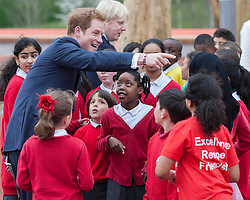 Prince Harry today joined Mayor of London Boris Johnson at the Olympic Park, London, United Kingdom. They officially opened a new playground for children and enjoyed some of the play obstacles on offer. Friday, 4th April 2014. Picture by i-Images<br /> <br /> Picture shows: Prince Harry with children.