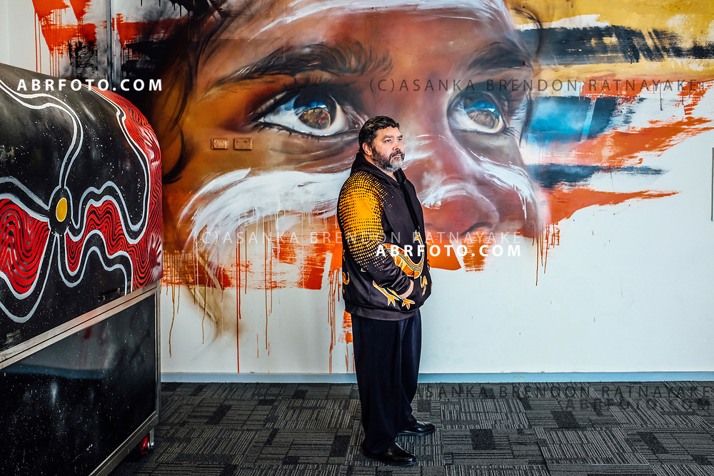 Troy Austin standing in front of an Aboriginal mural at the entrance of the Aboriginal Youth Sport and Recreation boxing gym on Gertrude Street in Melbourne, Australia, August 30, 2017. The Melbourne Aboriginal Youth Sport and Recreation centre was started by Troy's father Jock Austin to get Aboriginal youth away from drugs and to provide a safe environment for them to socialise whilst getting healthy. Asanka Brendon Ratnayake for the New York Times