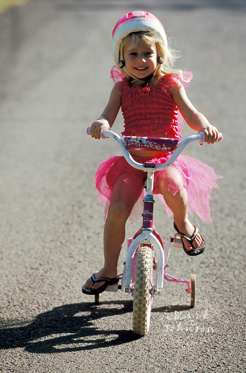 3 year old girl dressed all in pink, riding her bike