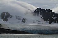 Glacier flows from mountains to sea shrouded by clouds in Smeerenburgfjorden on the north coast of Spitsbergen island; Svalbard, Norway.