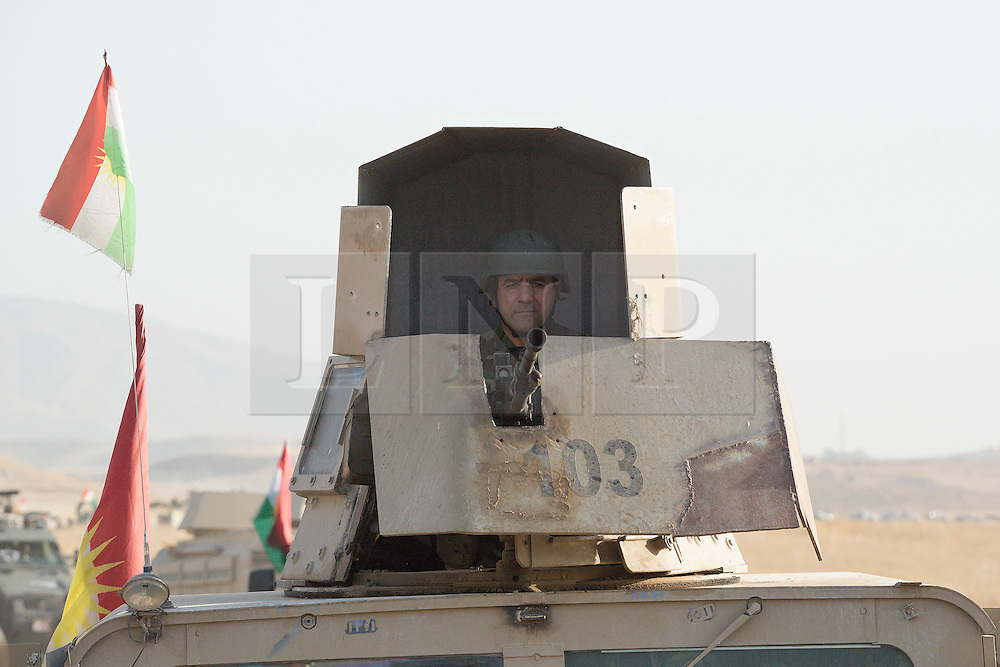 20/10/2016. Bashiqa, Iraq. A Kurdish peshmerga machine gunner hunkers down in the turret of his armoured Humvee as he takes part in a large offensive to retake the Bashiqa area from Islamic State militants today (20/10/2016).<br />