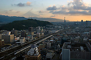 Mt Fuji can be seen in the distance as a bullet train passed through the station at Shizuoka City, Shizuoka Prefecture Japan on 01 Oct. 2012.  Photographer: Robert Gilhooly