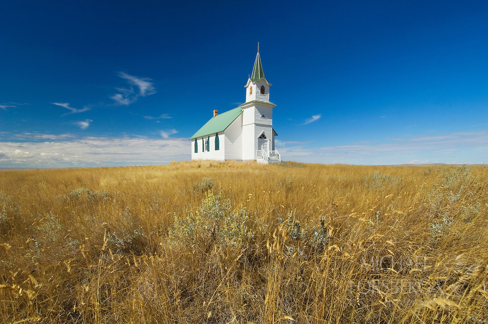 A county church in rural Montana stands alone in the open prairie.  Near Malta, Montana.