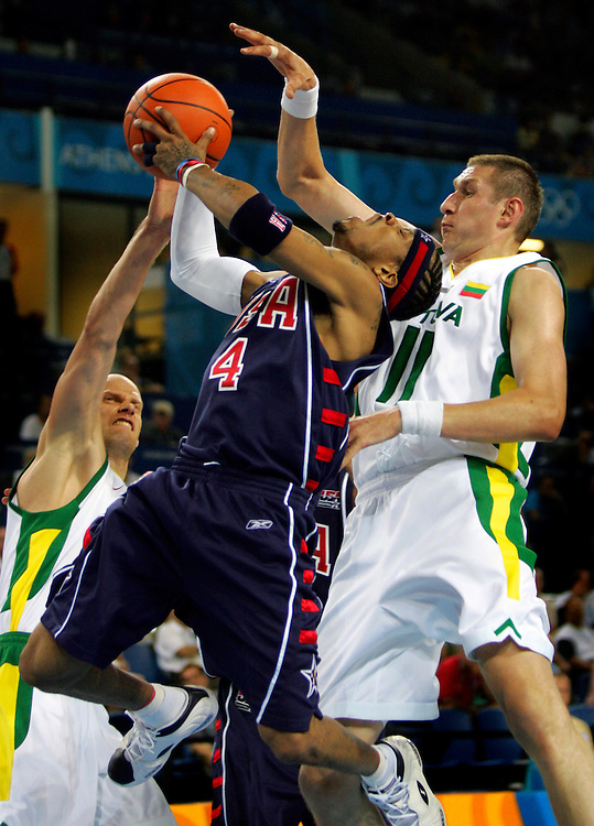 NBA star and United States Olympian Allen Iverson drove to the basket past the defense of Lithuania's Saulius Stombergas, left, and Eurelijus Zukauskas, right, in the 94-90 loss to the Lithuania men's basketball team at the Helliniko Indoor Arena in Athens, Greece. The loss was the second in four games for the United States team.
