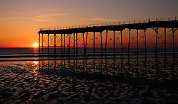© Licensed to London News Pictures.12/06/15<br /> Saltburn by the Sea, England<br /> <br /> The sun rises as dawn breaks over the pier at Saltburn by the Sea.<br /> <br /> Photo credit : Ian Forsyth/LNP