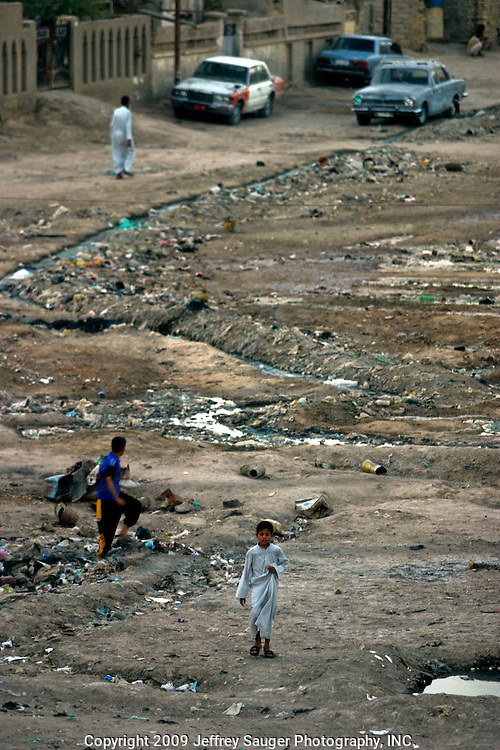 Evening brings activity along streets filled with garbage and zigzagging raw sewage in Nassiriyah, Iraq, Monday, August 11, 2003.