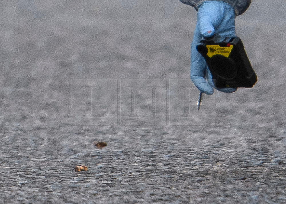 © Licensed to London News Pictures. 13/04/2019. London, UK. A police forensics officer videos bullets on the ground at the scene in Holland Park after shots were fired near the Ukrainian embassy. Photo credit: Ben Cawthra/LNP