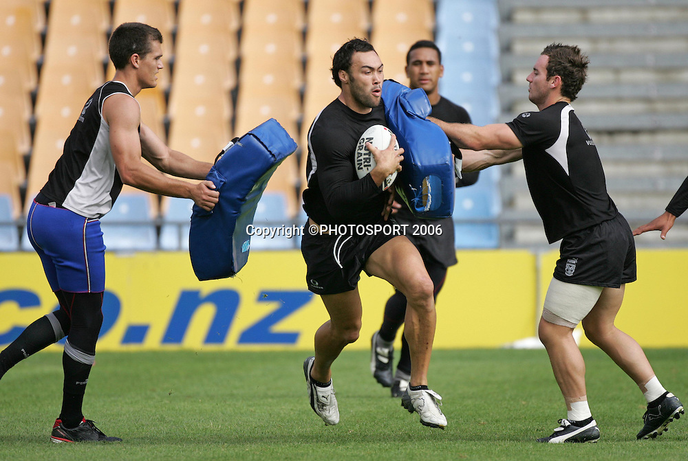 Warriors 2nd row Wairangi Koopu crashes through the tackle bags held by Todd Byrne (L) and Lance Hohaia (R) during the Vodafone Warriors training session held at Ericsson Stadium, Auckland, on Wednesday 5 April, 2006. Photo: Andrew Cornaga/PHOTOSPORT<br />