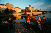 People enjoying sunset along Vltava River. Na?rodni Theatre on the left.