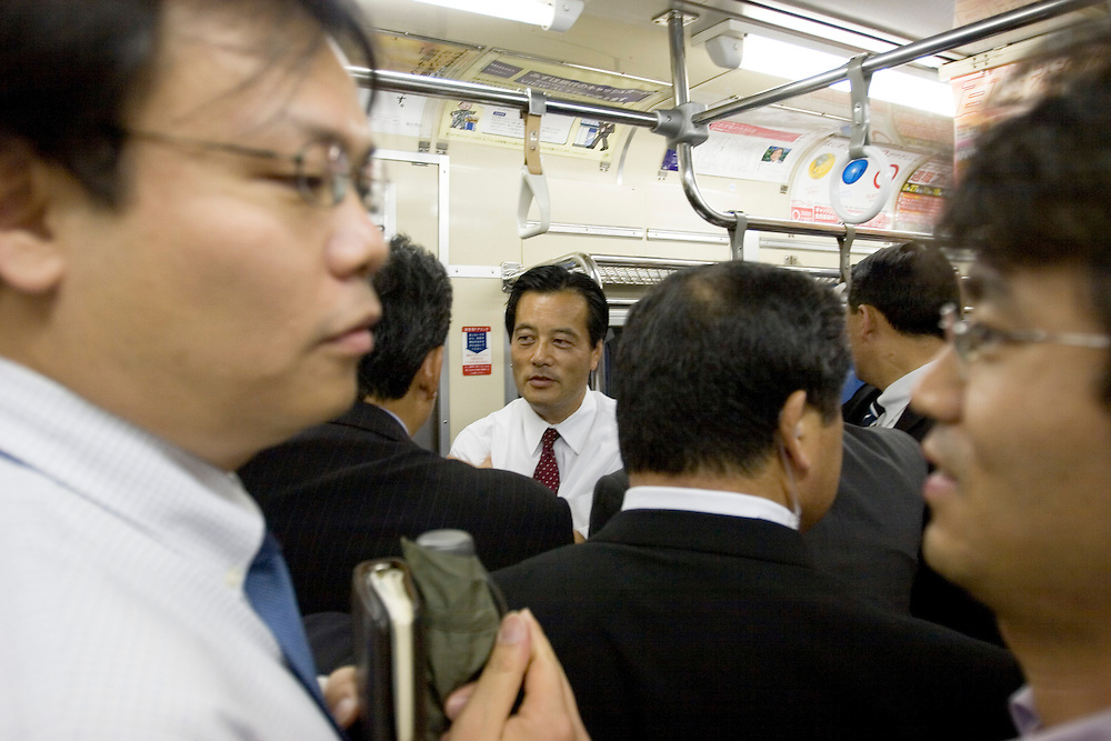 Katsuya Okada (white shirt) President of the Democratic Party of Japan speaks wit former DPJ president Hatoyama  on  a  tokyo  commuter  train after a rally  in support of  a  candidate for  the  lower house..