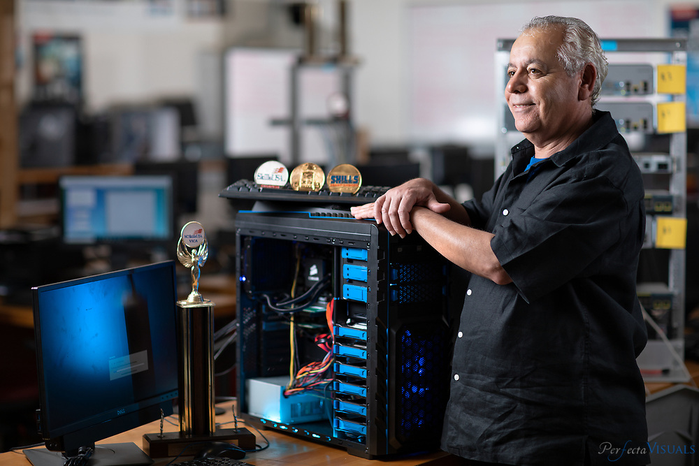 Reza Mohammadi consistently trains award winning students in his computer networking lab at Guilford County School's Weaver Academy. Photographed, Tuesday, May 8, 2018, in Greensboro, N.C. JERRY WOLFORD and SCOTT MUTHERSBAUGH / Perfecta Visuals<br /> <br /> <br /> <br /> During his 23 years of teaching at Weaver Academy, Reza Mohammadi often feels like a proud father.<br /> He&rsquo;s helped 10 of his students win national competitions in various categories of computer engineering technology, and he&rsquo;s taken more than 50 of his students from Guilford County to that same national stage.<br /> The competition is known as SkillsUSA Nationals, the Olympic trials for the country&rsquo;s top career and technical education students. To get there, students have to do well in North Carolina&rsquo;s SkillsUSA competition.<br /> But to even compete at the state level, they had to get the green light from Mohammadi. And Mohammadi is meticulous. <br /> He wants his students to be ready, and like some coach before a big game, he puts them through all sorts of exercises in his cavernous classroom full of computers.<br /> If they do well, Mohammadi knows what awaits his students. It could be a future where they can earn six-figure salaries and work for companies like Subaru and Lockheed-Martin.<br /> He&rsquo;s reminded of that future every time he walks into his classroom. It&rsquo;s right by the door. It&rsquo;s a bulletin board full of pictures and newspaper articles of his former students by the door. <br /> &ldquo;I&rsquo;ve accomplished something,&rdquo; he tells himself.<br /> He has -- more than his students really know.<br /> Mohammadi fled his home country of Iran 40 years ago to escape the political turmoil. He flew out on the last plane, he says, with only $500 in his pocket and a small bag that contained a few clothes and an American dictionary.<br /> Mohammadi was 18. He came to the United States by himself. He was a math whiz who couldn&rsquo;t speak a word of E