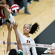 18 November 2017:  The San Diego State women's volleyball team closes out it's season against #24 Colorado State University. San Diego State middle blocker Deja Harris (15) attempts to spike the ball past CSU defenders in the first set. The Aztecs fell to the Rams in three sets. <br /> www.sdsuaztecphotos.com