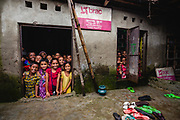 "Children looking out of a door and a window from inside a school classroom in a ""slum"" district"