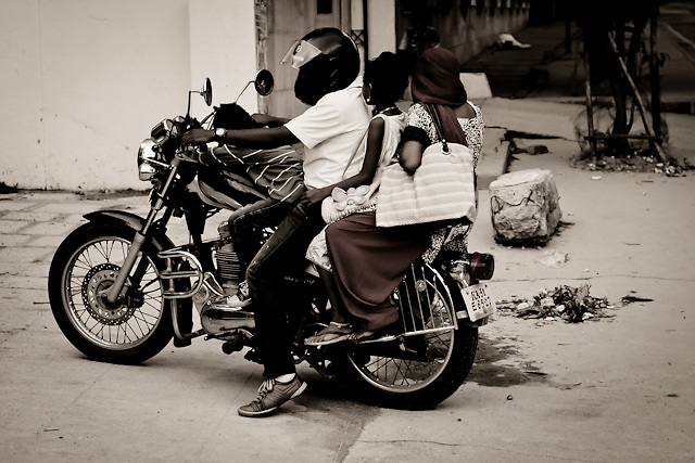 A father, mother and their daughter riding a motorcycle on Old Airport Road in Bangalore, India.