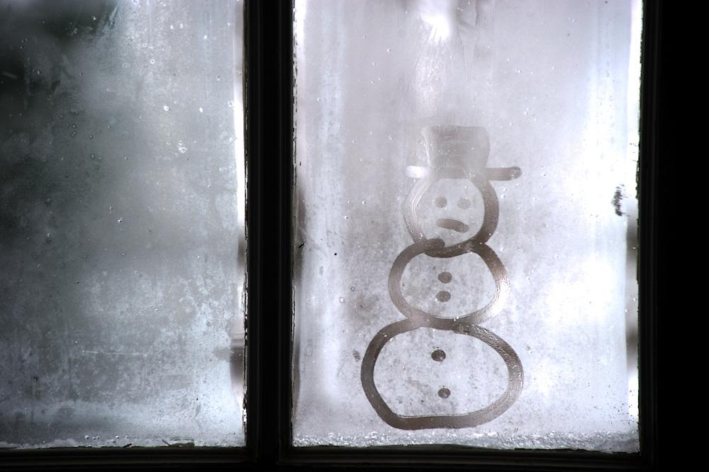 Snowman image on frosty window