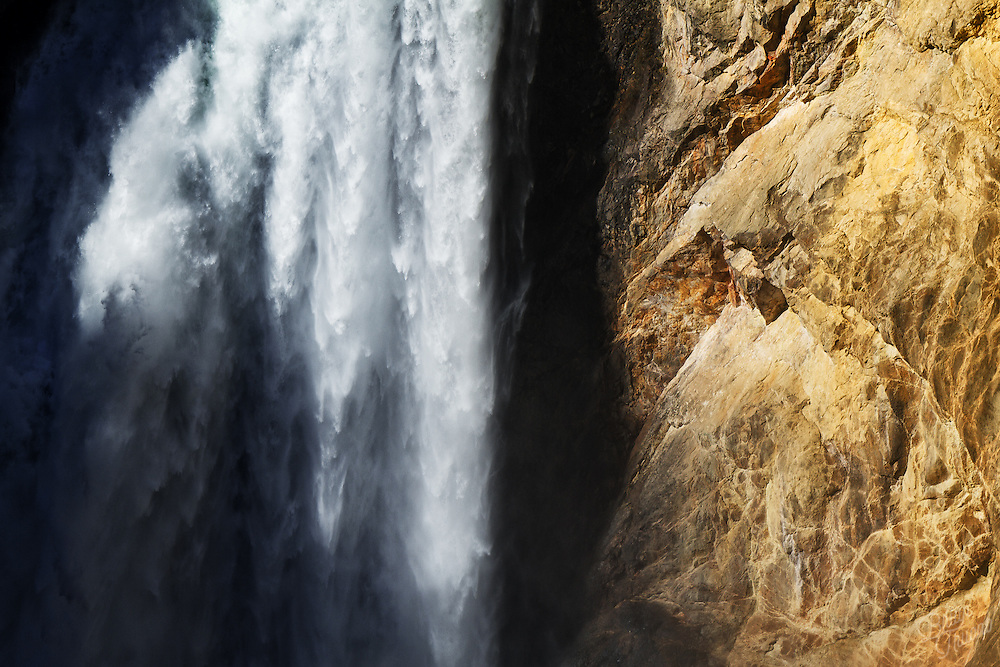 Water cascading down the past the golden cliffs at Lower Falls in Yellowstone National Park.