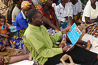 Villagers reading about Chorlton School, part of a project to link UK schools with those in Zambia, St Mary's, Monze, Zambia. PEPAIDS is a UK-based NGO whose mission is to promote and preserve the health of people in Zambia through the provision of support for HIV/AIDS initiatives and the promotion of awareness of issues surrounding HIV/AIDS. PEPAIDS' local partner NGO is SAPEP, based in the Monze and Mazabuka districts of the Southern Province of Zambia. They work together to empower the rural youth of Zambia to mobilise their communities to fight poverty and HIV/AIDS. SAPEP works with a large number of AIDS Action clubs (AACs) who are trained by SAPEP project staff in subjects such as peer education approaches; gender, customs and traditions; antiretroviral therapy; and counselling. This training empowers the AACs to support the communities in which they are based in the fight against HIV and AIDS. SAPEP encourages AACs to start income generating activities with the goal of being self-reliant and self-sufficient in their mission to alleviate HIV and AIDS. PEPAIDS has designed its training programme to form a cascade in order to reach as many people as possible. Peer educators participate in Training of Trainers workshops, with skills being passed on to club leaders and club members in turn to benefit the wider community. The entire programme is designed to be sustainable, youth-focused, participatory and culturally acceptable.