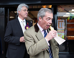© Licensed to London News Pictures . 03/11/2015 . Oldham , UK . UKIP leader NIGEL FARAGE (c) with candidate JOHN BICKLEY (l) eating pies outside Pound Bakery in Royton Shopping Centre , at the launch of the party's campaign for the seat of Oldham West and Royton . The by-election has been triggered by the death of MP Michael Meacher . Photo credit : Joel Goodman/LNP