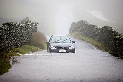 "© Licensed to London News Pictures. 27/01/2016. Hartsop UK. A stranded Mercedes is stuck in flood water on a road know as ""The Struggle"" just of the Kirkstone pass near Hartsop as Storm Jonas continues to batter the county. Photo credit: Andrew McCaren/LNP"