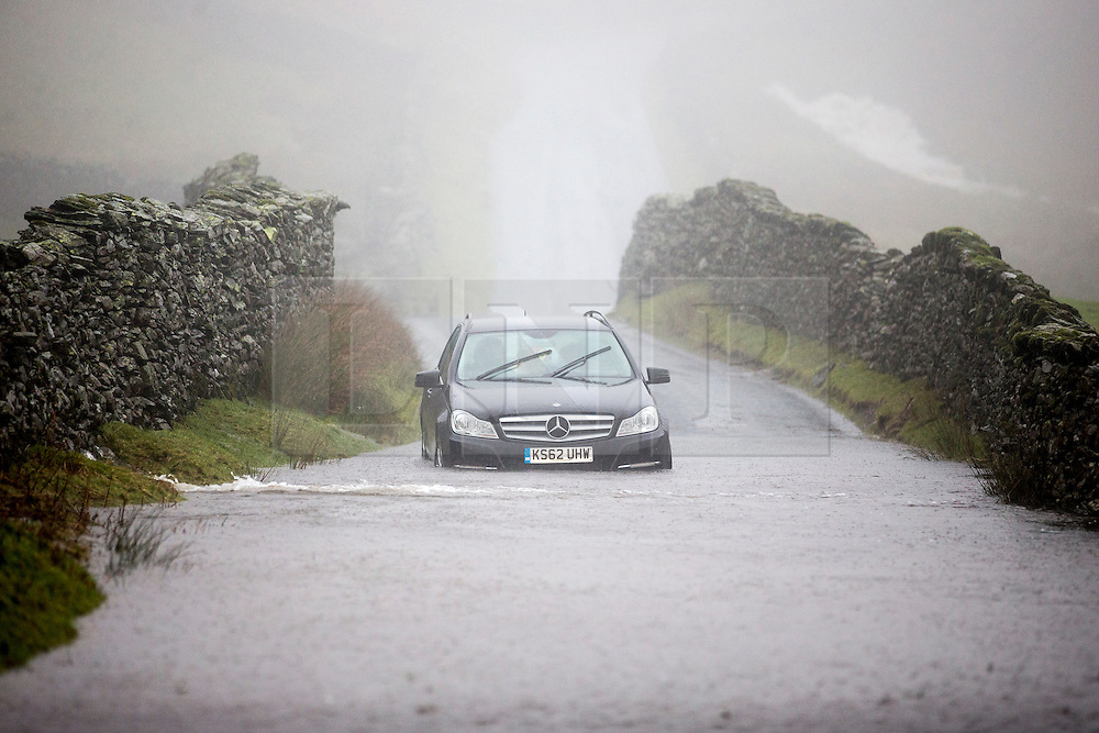"""© Licensed to London News Pictures. 27/01/2016. Hartsop UK. A stranded Mercedes is stuck in flood water on a road know as """"The Struggle"""" just of the Kirkstone pass near Hartsop as Storm Jonas continues to batter the county. Photo credit: Andrew McCaren/LNP"""