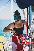 Jacki Arevalo hoists the main sail on baord the Grand Illusion II, while bareboating in the Exumas, Bahamas.
