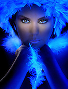Glowing portrait of a lady wearing a feather boa headpiece with a feather placed between her arms.Black light