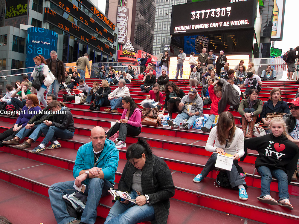 Crowd of tourists sitting on steps in Times Square Manhattan New York USA