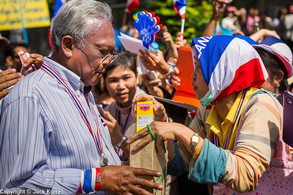 21 JANUARY 2014 - BANGKOK, THAILAND:  A woman stops SUTHEP THAUGSUBAN to give him a bottle of Perskindol, an over the counter muscle relaxer, during a march down Thanon Naradhiwas Rajanagarindra in the financial district of Bangkok. Suthep, the leader of the anti-government protests and the People's Democratic Reform Committee (PDRC), the umbrella organization of the protests, led a march through the financial district of Bangkok Tuesday. Shutdown Bangkok has entered its second week with no resolution in sight. Suthep is still demanding the caretaker government of Prime Minister Yingluck Shinawatra resign and the PM says she won't resign and intends to go ahead with the election.    PHOTO BY JACK KURTZ