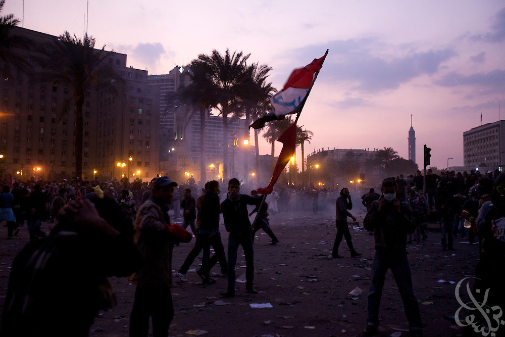 An Egyptian protestors defiantly wave an Egyptian flag as tear gas canisters fired by nearby security forces burn behind during street battles November 21, 2011 in Tahrir square  in central Cairo, Egypt. Thousands of protestors demanding the military cede power to a civilian government authority clashed with Egyptian security forces for a third straight day in Cairo, with hundreds injured and at least 24 protestors killed.  (Photo by Scott Nelson)