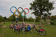 Cyclists rest at the Olympic rings, a legacy of the London 2012 Olympics, on 16th August 2017, in the Queen Elizabeth Olympic Park, Stratford, East London, England.