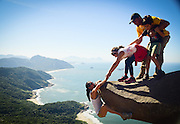 The amazing photo of fitness fanatic, Luis Fernando Candela, in what appeared as him hanging upside down above a 1000 foot drop, has attracted many visitors to the same spot on a beach at Pedra Do Telegrafo in Brazil. The heart-stopping shot was revealed to be a trick of the camera, as there is in fact a plateau directly below the rock where people can stand.<br />  <br /> Photographer, Vivianne Montalvao has captured people striking similar poses on the rock. People have flocked from all over the place to the rock, in hopes their photos also make them look like fearless daredevils<br /> ©Exclusivepix Media